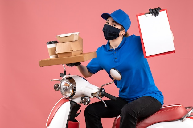 Front view female courier in mask with food delivery on pink