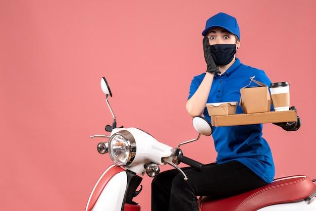 Corriere femminile di vista frontale in maschera con la consegna del cibo sul rosa