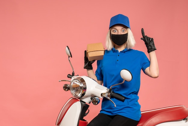 Front view female courier in mask with little food package on light pink