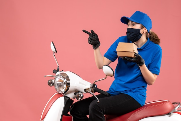 Front view female courier in mask with little food package on pink