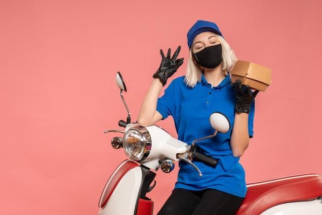 Corriere femminile vista frontale in maschera con poca confezione di cibo sul rosa