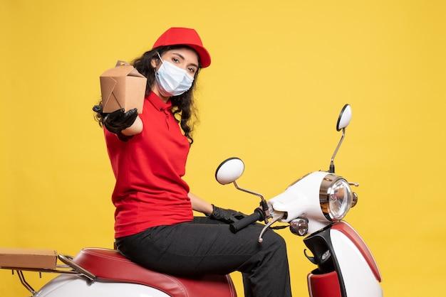 Corriere femminile vista frontale in maschera con piccolo pacchetto di cibo su sfondo giallo servizio pandemia lavoratore uniforme covid consegna lavoro