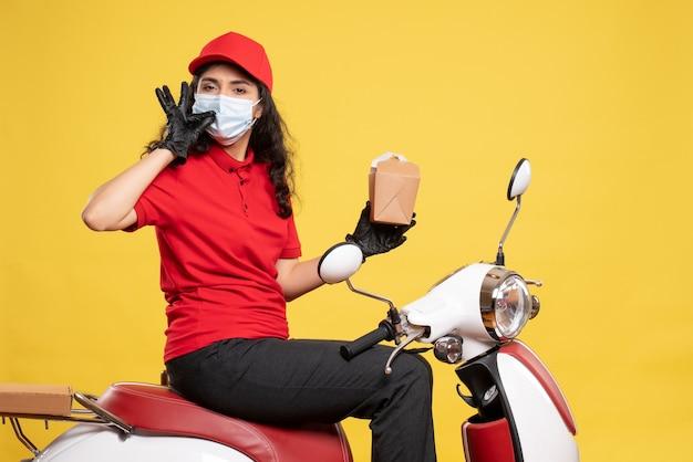 Corriere femminile vista frontale in maschera con piccolo pacchetto di cibo sul servizio di scrivania giallo uniforme da lavoratore pandemico covid- consegna di lavoro