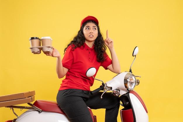 黄色の背景にコーヒー カップを保持している自転車の女性宅配便の正面図ワーカー サービス制服女性配達作業