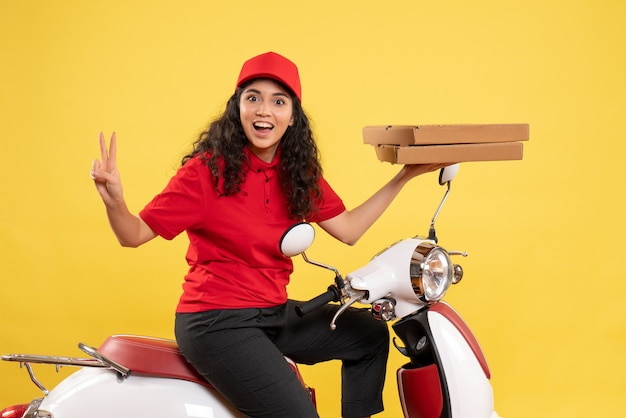 黄色の背景にピザの箱を保持している自転車の正面女性宅配便の制服労働者の女性配達員