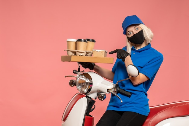 Курьер-женщина, вид спереди на велосипеде с кофейными чашками на розовом