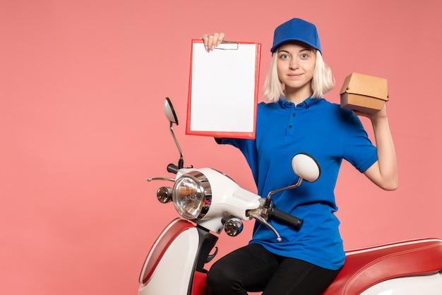 Курьер-женщина, вид спереди на велосипеде с небольшим пакетом еды на розовом