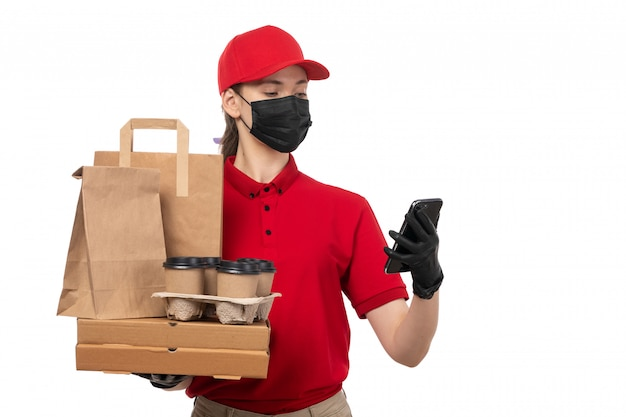 A front view female courier in red carp red shirt black gloves and black mask holding food packages and coffee cups using a phone on whiteservice