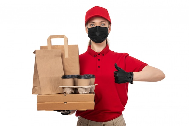A front view female courier in red carp red shirt black gloves and black mask holding food packages and coffee cups on white
