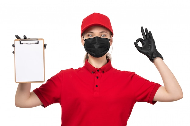 A front view female courier in red carp red shirt black gloves and black mask holding notepad and posing on white