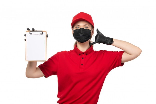 A front view female courier in red carp red shirt black gloves and black mask holding notepad and showing phone call sign on white