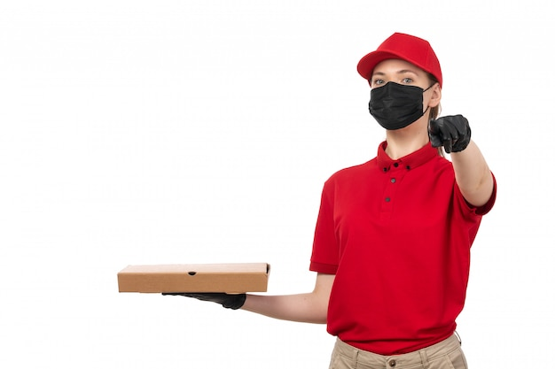 A front view female courier in red carp red shirt black gloves and black mask holding pizza box pointing finger on white