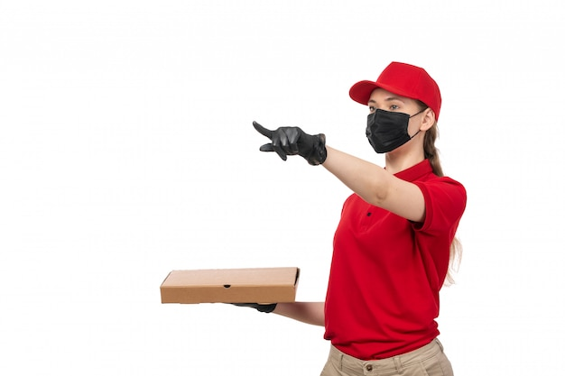 A front view female courier in red carp red shirt black gloves and black mask holding pizza box on white
