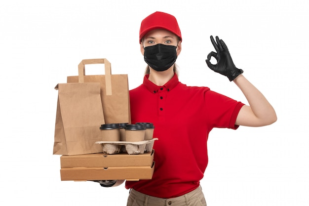 A front view female courier in red carp red shirt black gloves and black mask holding pizza boxes and coffee cups pointing finger on white