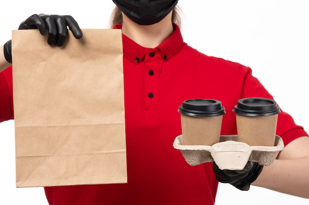 A front view female courier in red shirt andb lack glvoes holding coffee cups and package with food