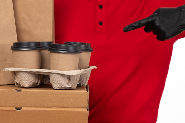 A front view female courier in red shirt black gloves holding boxes and coffee cups