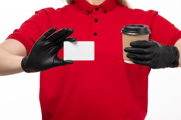 A front view female courier in red shirt black gloves holding cup with coffee and white card on white