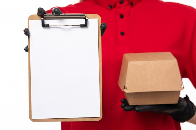 A front view female courier in red shirt and black gloves holding notepad and package with food