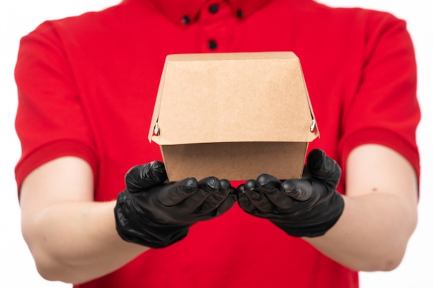A front view female courier in red shirt and black gloves holding package with food uniform