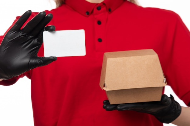 A front view female courier in red shirt black gloves holding white card package on white