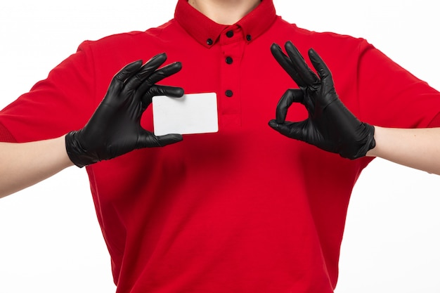 A front view female courier in red shirt and black gloves holding white card posing on white