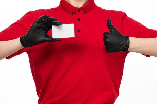 A front view female courier in red shirt and black gloves holding white card on white