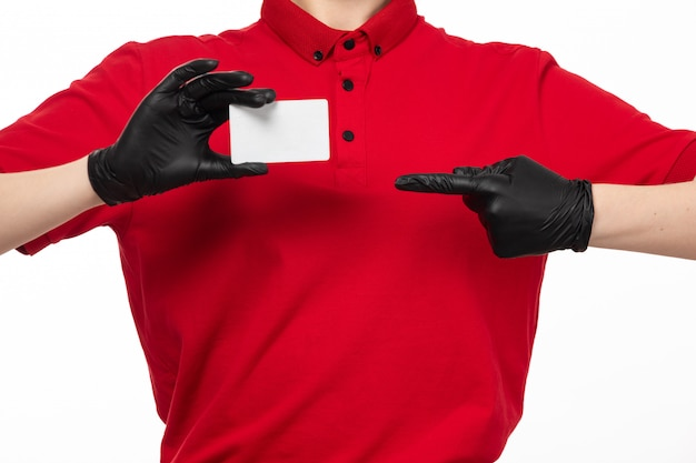A front view female courier in red shirt black gloves holding white card