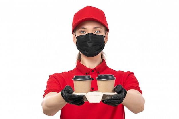 A front view female courier in red shirt red cap black gloves and black mask holding coffee cups