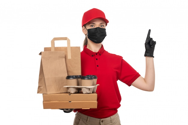 A front view female courier in red shirt red cap black gloves and black mask holding coffee and food packages on white