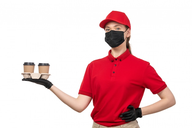 A front view female courier in red shirt red cap black gloves and black mask holding coffee