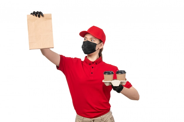 A front view female courier in red shirt red cap black gloves and black mask holding food package and coffee on white