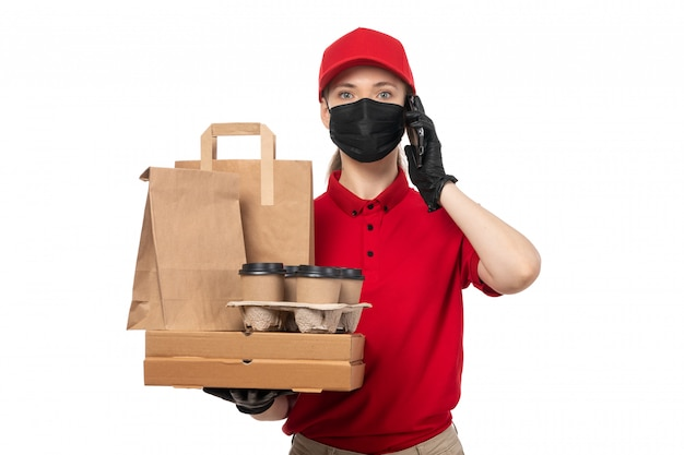 A front view female courier in red shirt red cap black gloves and black mask holding pizza boxes and coffee cups on white