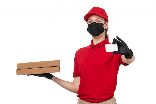 Un corriere femminile di vista frontale in guanti rossi della camicia rossa della camicia rossa e scatole nere della pizza della tenuta della maschera che mostrano carta bianca su bianco
