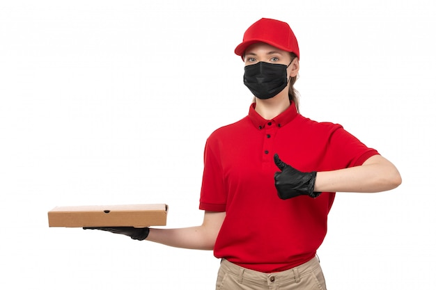 A front view female courier in red shirt red cap black gloves and black mask holding pizza boxes on white
