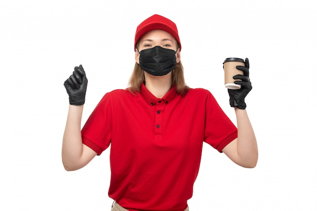 A front view female courier in red shirt red cap black gloves holding coffee on white