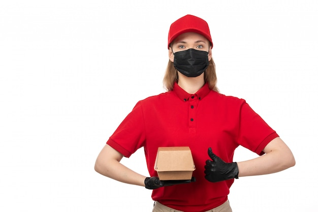 A front view female courier in red shirt red cap black gloves and mask holding package with food on white