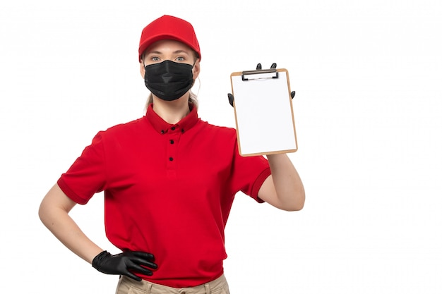 A front view female courier in red shirt red capblack gloves and black mask holding notepad on white