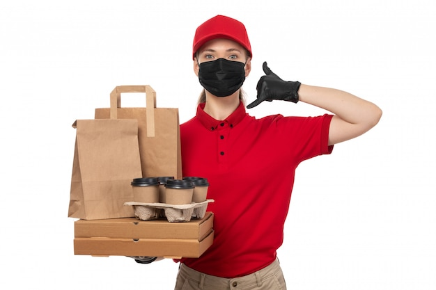 A front view female courier in red shirt red capblack gloves and black mask holding pizza boxes and coffee cups on white