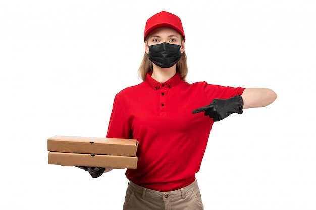 A front view female courier in red shrit red cap black gloves and black mask holding pizza boxes on white