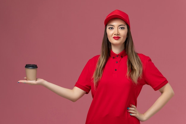Front view female courier in red uniform and cape holding delivery coffee cup on pink background service delivery uniform worker