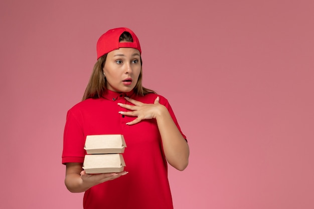 Front view female courier in red uniform and cape holding delivery food package on light-pink background uniform delivery service company job work