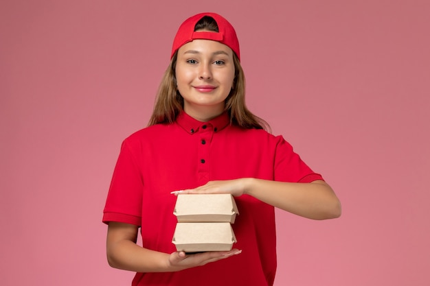 Front view female courier in red uniform and cape holding delivery food package on light-pink background uniform delivery service company job worker