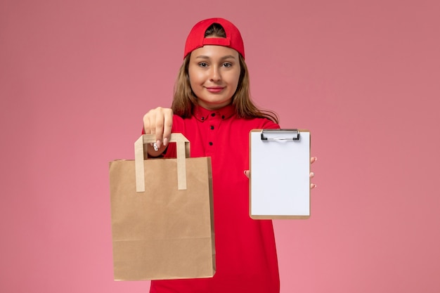 Corriere femminile di vista frontale in uniforme rossa e mantello che tiene il pacchetto di cibo per la consegna e blocco note sulla parete rosa chiaro, servizio di consegna uniforme