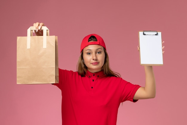 Front view female courier in red uniform and cape holding delivery food package and notepad on pink wall, uniform delivery job service