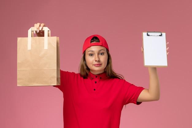 Corriere femminile di vista frontale in uniforme rossa e mantello che tiene il pacchetto di cibo di consegna e blocco note sulla parete rosa, servizio di lavoro di consegna uniforme