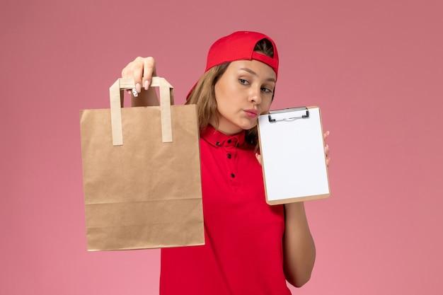 Corriere femminile di vista frontale in uniforme rossa e mantello che tiene il pacchetto di cibo di consegna e blocco note pensando sulla parete rosa chiaro, servizio di lavoro di consegna uniforme