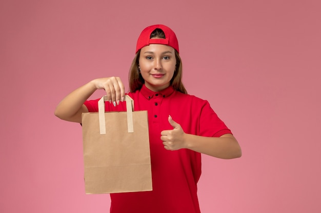 Front view female courier in red uniform and cape holding delivery food package on the pink background uniform delivery job service work