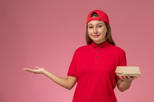 Front view female courier in red uniform and cape holding delivery food package on the pink background uniform delivery service company girl