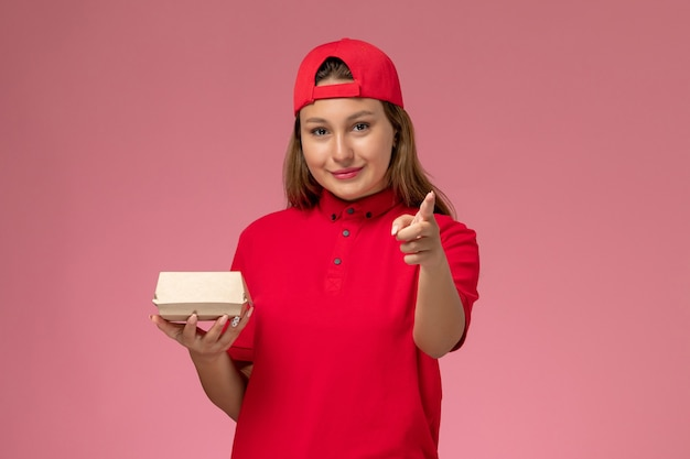Front view female courier in red uniform and cape holding delivery food package on pink background uniform delivery service company job work worker