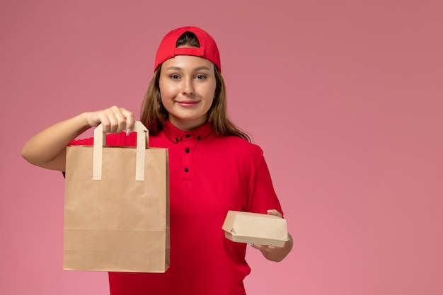 Front view female courier in red uniform and cape holding delivery paper food packages on the pink wall, uniform delivery service